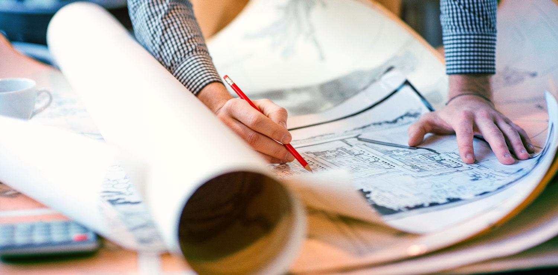 man writing on blueprints
