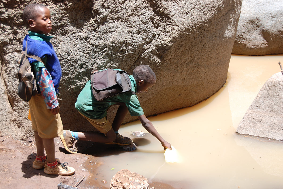 Boys Collecting Water from Contaminated River